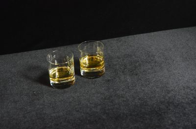 Two glasses of whiskey on a gray surface in front of a black wall.